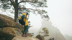 El hombre en chaqueta amarilla sube las rocas en las montañas del invierno metrajes