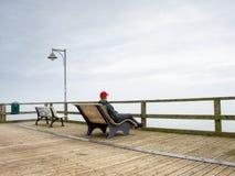 El hombre en chaqueta caliente y la gorra de béisbol se sientan en el embarcadero de madera y gozan del mar reservado de la mañan Fotografía de archivo libre de regalías