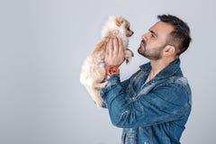 El hombre en chaqueta del dril de algodón sostiene el perro pomeranian fotografía de archivo