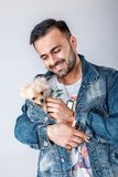 El hombre en chaqueta del dril de algodón sostiene el perro pomeranian fotos de archivo
