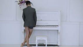 El hombre en chaqueta y calzoncillos juega el piano en el fondo blanco Visión trasera Concepto talentoso del músico Pianista en b metrajes