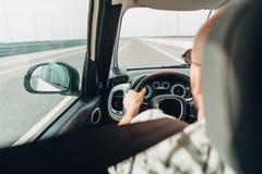 El hombre en el coche que viaja en el camino Fotos de archivo