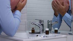 El hombre en cuarto de baño cerca de algunas píldoras de la medicina comprueba la caja del correo electrónico del teléfono móvil metrajes