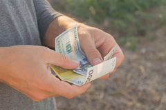 El hombre en cuello alto gris se sostiene en billetes de banco de los brazos del dólar y del euro Foto de archivo
