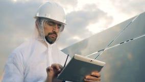 El hombre en desgaste de la protección está actuando una tableta al lado de una instalación solar masiva almacen de metraje de vídeo