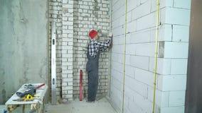 El hombre en desgaste del trabajo y casquillo rojo instala el carril del metal sobre la pared del bloque de cemento almacen de metraje de vídeo