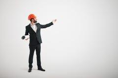El hombre en desgaste formal y un casco de la construcción señalan su towa de la mano Fotos de archivo libres de regalías