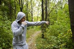 El hombre en el bosque, entrenando en el boxeo imagen de archivo