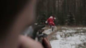 El hombre en el bosque que apunta un rifle en Santa Claus almacen de metraje de vídeo