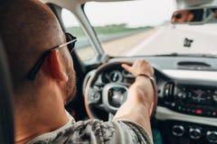 El hombre en el coche que viaja en el camino Fotografía de archivo libre de regalías