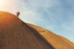 El hombre en el desierto sube en la duna Imagen de archivo libre de regalías