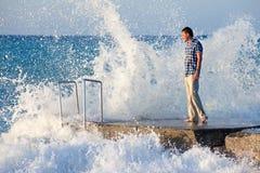 El hombre en el embarcadero y la onda grande con salpica Imagen de archivo