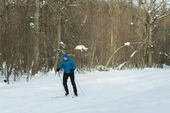 El hombre en el esquí a campo través en bosque del invierno Foto de archivo