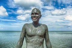 El hombre en el fango al día soleado en el mar Imagen de archivo