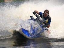 El hombre en el jet-esquí da vuelta muy rápidamente con el salto Imágenes de archivo libres de regalías