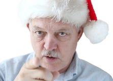 El hombre en el sombrero de Papá Noel le está mirando Imagen de archivo