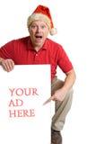 El hombre en el sombrero de Santa y la camisa roja lleva a cabo una muestra del anuncio Imagenes de archivo