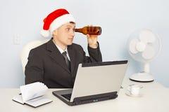 El hombre en el sombrero del Año Nuevo mira a través de una botella Imagenes de archivo