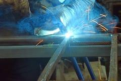 El hombre en el trabajo, barras de metal soldado con autógena del soldador Imagen de archivo libre de regalías