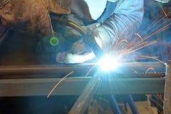 El hombre en el trabajo, barras de metal soldado con autógena del soldador Foto de archivo libre de regalías