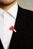 El hombre en el traje negro con el corazón rojo Imágenes de archivo libres de regalías