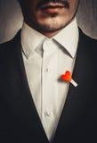 El hombre en el traje negro con el corazón rojo Imagen de archivo libre de regalías