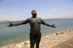 El hombre en fango en el mar muerto Imagenes de archivo
