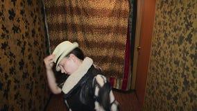 El hombre en gafas de sol baila en pasillo con la muchacha en vestido del sombrero parodiar Diversión metrajes