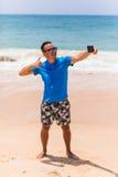 El hombre en gafas de sol se sienta con un smartphone en las manos y selfie de la fabricación en el teléfono cerca del mar Imagen de archivo
