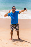 El hombre en gafas de sol se sienta con un smartphone en las manos y selfie de la fabricación en el teléfono cerca del mar Imagen de archivo libre de regalías