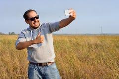 El hombre en gafas de sol tira el selfie en el campo Foto de archivo