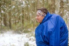 El hombre en el impermeable azul en el bosque foto de archivo