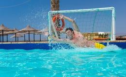 El hombre en la acción salta la meta en la piscina que juega water polo Foto de archivo