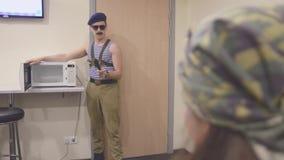 El hombre en la camisa y el casquillo marinos, gafas de sol abre microonda con el cuchillo en manos Discurso surrealism almacen de metraje de vídeo