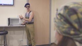 El hombre en la camisa y el casquillo marinos, gafas de sol cierra microonda con el cuchillo en manos Discurso surrealism almacen de video
