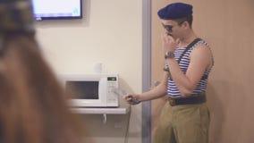 El hombre en la camisa y el casquillo marinos, gafas de sol permanece en la microonda con el cuchillo en manos Discurso surrealis almacen de video