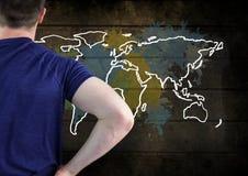 El hombre en la camiseta que mira el mapa colorido con la pintura salpica en fondo de la pared imagen de archivo libre de regalías