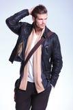 El hombre en la chaqueta de cuero está mirando lejos a su lado y sonríe Foto de archivo libre de regalías