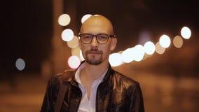 El hombre en la chaqueta de cuero y el café de las bebidas de los vidrios en la calle en la noche metrajes