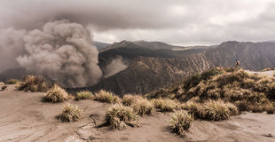 El hombre en la colina está mirando en la erupción del volcán de Bromo Imagen de archivo libre de regalías