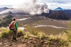 El hombre en la colina está mirando en la erupción del volcán de Bromo Parque nacional de Bromo Tengger Semeru Foto de archivo libre de regalías