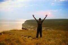 El hombre en la costa cuesta, levantando las manos ascendentes Fotografía de archivo