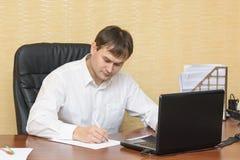 El hombre en la escritura de la oficina en el papel Fotos de archivo libres de regalías