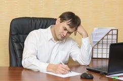 El hombre en la escritura de la tabla en el papel Fotos de archivo