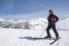 El hombre en la forma del montaña-esquí contra las montañas Imagen de archivo libre de regalías