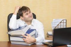 El hombre en la mano de la oficina rasguña su cabeza Fotografía de archivo