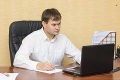 El hombre en la oficina en el ordenador para ver el documento Imagenes de archivo