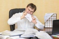 El hombre en la oficina en los dientes de la desesperación que rasgan el papel Imagen de archivo