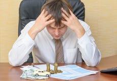 El hombre en la oficina, llevando a cabo su cabeza que mira el aviso del accidente con el dinero y la máquina que mienten en el d Foto de archivo