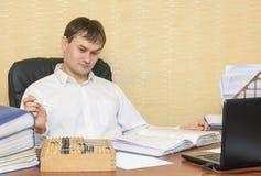 El hombre en la oficina mira cuentas Imagen de archivo libre de regalías